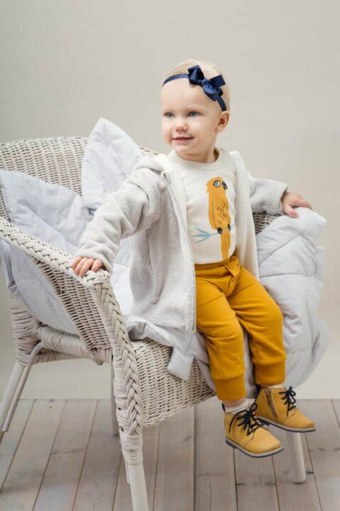 Sitzendes Mädchen trägt weißen Babybody langarm mit Papagei - Currygelbe Babyhose mit Knöpfe & Patch Papagei - Beige Kapuzen Sweatshirt Flauschjacke von Pinokio - Babyphoto