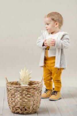 Stehender Junge trägt beige Kapuzen Plüschjacke Flausch - Weißen Baby Langarmbody mit Papagei Motiv - Currygelbe Babyhose mit Knöpfe & breitem Komfortbund von Pinokio - Kinderphoto