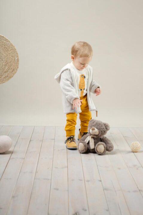 Stehender Junge trägt senfgelbe Babyhose mit Knöpfe - Weißen Papagei Babybody langarm - Plüschjacke mit Reißverschluss & Kapuze in Beige von Pinokio - Kinderphoto
