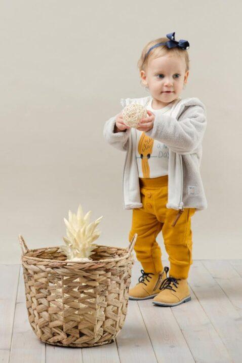 Stehendes Mädchen trägt weißen Baby Langarmbody mit Papagei - Senfgelbe Babyhose mit Knöpfe & breitem Komfortbund - Beige Kinder Flausch Plüschjacke mit Kapuze & Reißverschluss von Pinokio - Babyphoto