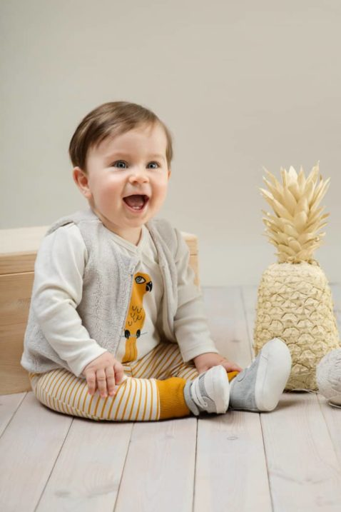 Lachender sitzender Junge trägt weißen Baby Wickelbody mit Papagei Motiv - Senfgelbe Streifen Leggings mit Schlupfbund - Plüschweste mit Reißverschluss Beige von Pinokio - Babyphoto