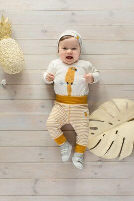 Liegender lachender Junge trägt currygelb weiß gestreifte Leggings Schlafhose - Weißen Baby Wickelbody mit Papagei - Kinder Mütze Papagei in Beige von Pinokio - Babyphoto