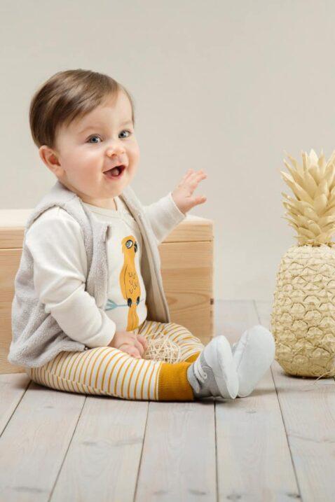 Sitzender Junge trägt currygelb weiss gestreifte Baby Leggings Sweathose - Wickelbody weiß mit Papagei Motiv - Flauschweste Beige von Pinokio - Babyphoto