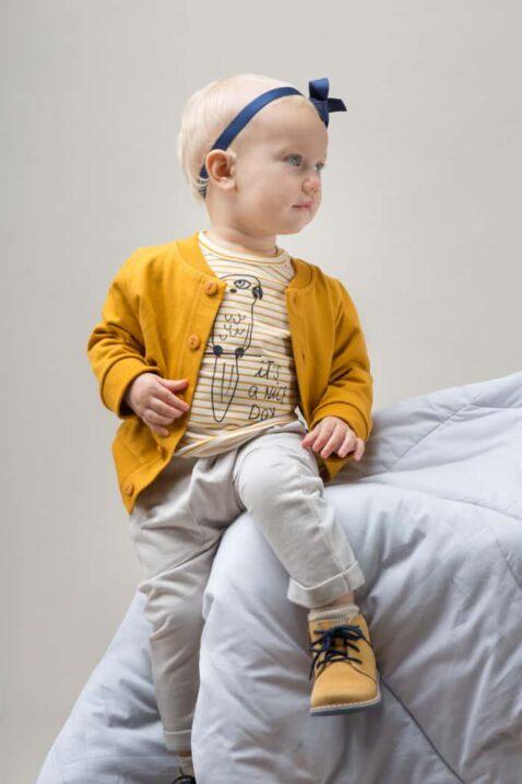Mädchen trägt Baby Sweatjacke Cardigan mit Knöpfen - Gestreiftes weiß-senfgelbes Langarmshirt mit Papagei - Beige helle Babyhose Pumphose mit Taschen von Pinokio - Babyphoto