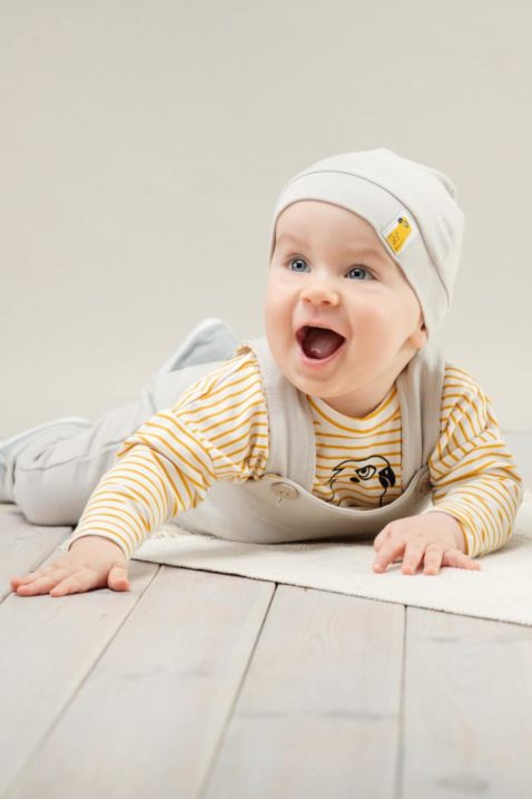 Krabbelnder lachender Junge trägt beige Baby Latzhose mit Tasche - Beige Babymütze mit Patch Papagei - Baby Langarmshirt currygelb weiß gestreift mit Papagei von Pinokio - Babyphoto