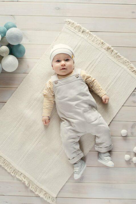 Liegender Junge trägt helle beige Baby Latzhose mit Tasche - Baby Mütze beige mit Papagei Patch - Baby Langarmshirt Oberteil Streifen currygelb weiß mit Papagei Motiv von Pinokio - Babyphoto