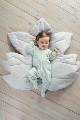 Liegender lächelnder Junge trägt hellblauen weissen Baby Langarm Schlafstrampler mit Fuß im Streifen Look & Papagei Patch - Türkis gestreifter Schlaf Overall für Kinder von Pinokio - Babyphoto