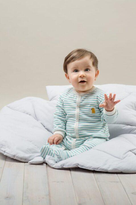 Sitzender staunender Junge trägt weiss türkis blau gestreiften Baby Langarm Schlafstrampler langarm mit Füßenim & Papagei Patch - Streifen Kinderschlafanzug Schlafoverall von Pinokio - Babyphoto