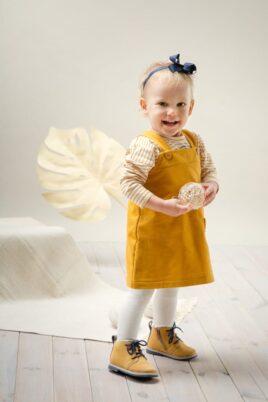 Lachendes Baby Mädchen trägt currygelbes Kinder Kleid Babykleidchen mit Tasche - Gestreiftes gelb ecru weißes Langarmshirt mit Papagei für Sommer & Herbst von Pinokio - Babyphoto