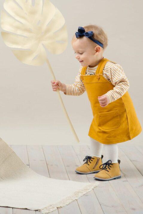 Spielendes Baby Mädchen trägt kurzes Kinder Baumwollkleid Latzkleid in Currygelb - Gestreiftes Shirt Oberteil mit langen Ärmeln & Papagei Motiv von Pinokio - Babyphoto