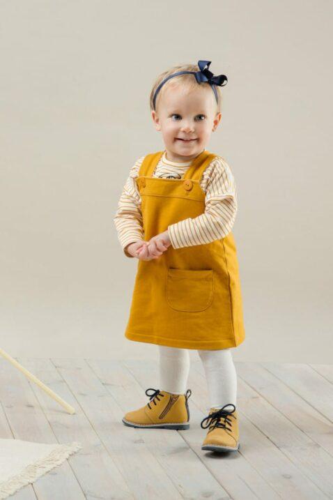 Stehendes Baby Mädchen trägt langes Oberteil Shirt mit Papagei Streifen-Look - Currygelbes Sweatkleid aus Baumwolle mit Taschen für Frühling, Sommer, Herbst von Pinokio - Babyphoto