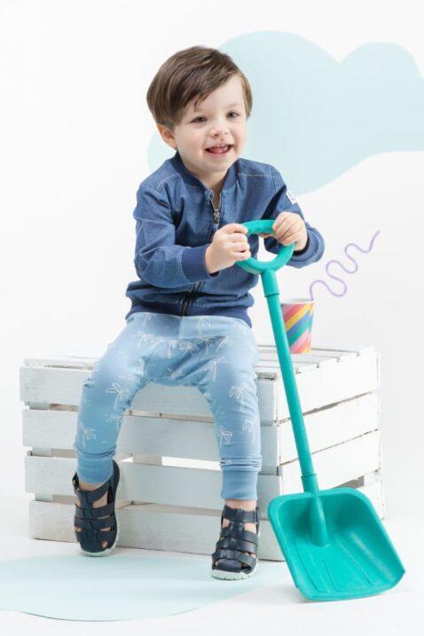 Sitzender lachender Junge mit Schaufel trägt blaue Leggings Sweathose mit weißen Palmen - Babyjacke in Jeansoptik mit Patch Bomber von Pinokio - Kinderphoto