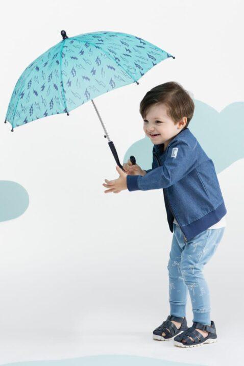 Stehender lachender Junge mit Schirm trägt blaue Babyjacke Bomberjacke in Jeans-Optik Sommerjacke - Hellblaue Leggings Schlupfhose mit weißen Palmen von Pinokio - Kinderphoto