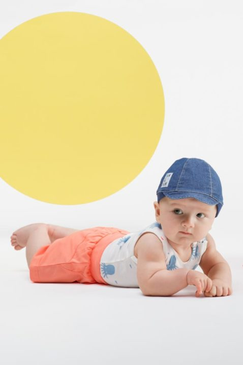 Baby Junge trägt weißen Babybody ohne Arm mit Tintenfische - Kurze Hose Shorts mit Patch & Kordel in Koralle - Blaue Schirmmütze im Jeans Look von Pinokio - Babyphoto