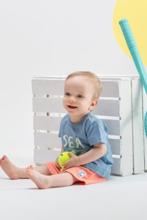 Sitzender lachender Junge trägt blaues Kinder T-Shirt kurzarm SEA Motiv - Orange koralle rote kurze Sommer Babyshorts mit Kordel & Patch von Pinokio - Kinderphoto Babyphoto