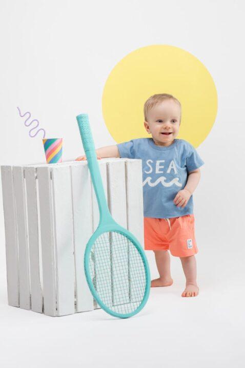 Stehender lächelnder Junge trägt orange lachsfarbene Baby kurze Hose mit Patch - Blaues T-Shirt mit Aufschrift SEA & Wellen Meer von Pinokio - Kinderphoto Babyphoto