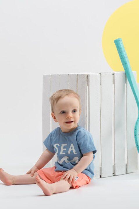 Sitzender Junge trägt blaues kurzarm Babyshirt Kinder mit Sommer SEA Motiv - Korall Orange rote Shorts mit weißem Patch SUN & FUN von Pinokio - Kinderphoto Babyphoto