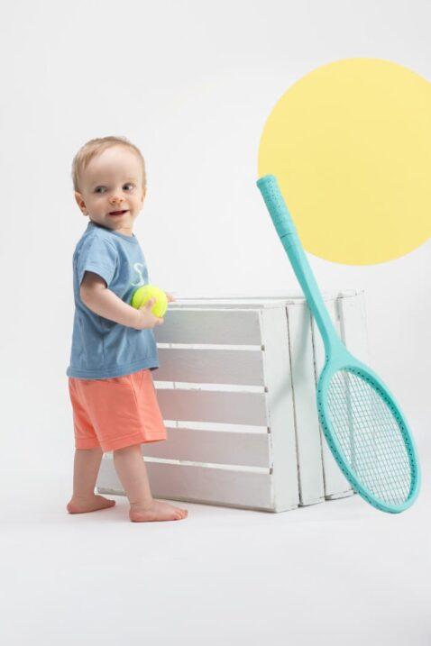 Stehender Junge trägt koralle Baby Sommer Shorts mit Patch - Blaues T-Shirt mit SEA Aufschrift & Meereswellen von Pinokio - Kinderphoto Babyphoto
