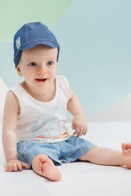 Sitzender staunender Junge trägt blaue kurze Hose mit Palmen - Tank Top ärmellos mit Insel, Meer & Sonne in Weiß - Baby Mütze mit Schirm & Patch in Dunkelblau von Pinokio - Babyphoto