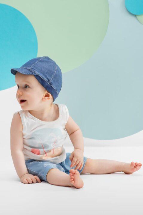 Sitzender lachender Junge trägt weißes Tank-Top Oberteil mit Insel - Sommerhose blaue Shorts mit Palmeln & Patch - Blaue Sommer Baby Schirmmuetze in Jeans von Pinokio - Babyphoto