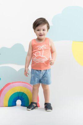 Stehender lachender Junge trägt Baby Kinder kurze Hose Shorts in Blau - Tank-Top mit Palme, Insel, Sonne in Koralle Orange Sommer von Pinokio - Kinderphoto Babyphoto