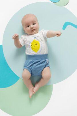Liegender Junge trägt weißen Sommer Wickelbody kurzarm mit Zitrone Lemonade - Blauen Baby Bloomer kurz mit Patch Windelhose Windelabdeckung Babyhose von Pinokio - Babyphoto