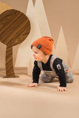 Krabbelnder Junge trägt graue Baby Latzhose Schottenkaro - Schwarzer Body in Polo-Optik mit Bär - Braun orangene Babymütze mit Umschlag von Pinokio - Babyphoto