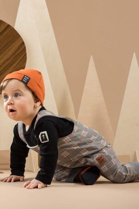 Krabbelnder Junge trägt Baby Latzhose Trägerhose in Tartan Southdown Grey - Body Polo schwarz mit Bär - Baby Mütze mit Umschlag in Orangebraun von Pinokio - Babyphoto