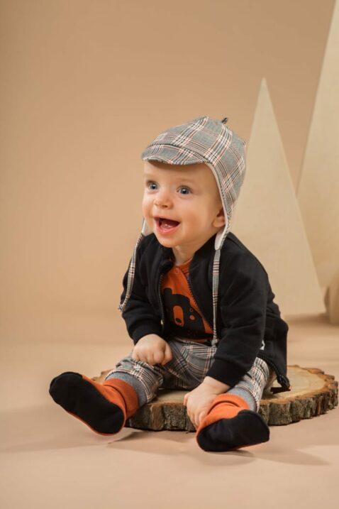 Sitzender Junge trägt graue Baby Leggings Sweathose Schottenkaro - Orange Braun Bär Wickelbody - Schwarze Sweatjacke - Pilotenmütze Schottenmuster von Pinokio - Babyphoto