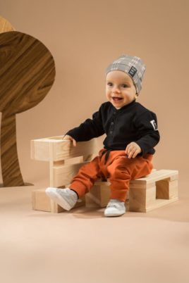 Sitzender Junge trägt rost braune Pumphose mit Taschen - Schwarzer Baby Body in Polo-Optik Patch & Knöpfe - Mütze im Schottenmuster grau Southdown Grey von Pinokio - Babyphoto