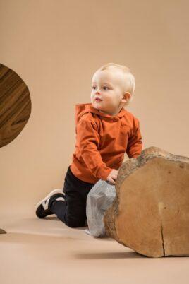 Kniender Junge trägt schwarze Baby Pumphose mit Knöpfe - Braun orange Kapuzenpullover Hoodie mit asymmetrischer Knopfleiste Patch BEAR CLUB von Pinokio - Babyphoto Kinderphoto
