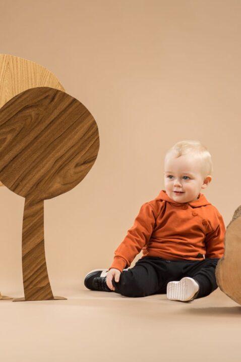 Sitzender Junge trägt orange braunen Baby Hoodie Sweatshirt Kapuzenpullover - Schwarze Pumphose mit Tasche & Patch BEAR Club von Pinokio - Babyphoto Kinderphoto