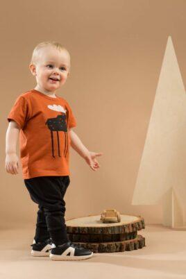 """Stehender lachender Junge trägt schwarze Babyhose Pumphose mit Knöpfe & Patch - T-Shirt mit Elch & Schriftzug """"ADVENTURE"""" orange braun von Pinokio - Babyphoto Kinderphoto"""