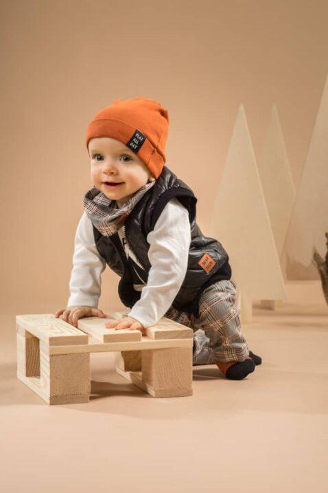 Junge trägt braune Babymütze mit Umschlag & Patch - Kurze Steppweste schwarz - Weißer Wickelbody Camping - Halstuch Loop Schlauchschal Multifunktionstuch im Schottenmuster von Pinokio - Babyphoto Kinderphoto