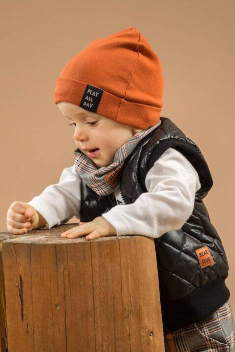Junge trägt gemustertes Baby Multifunktions Halstuch grau - Weißen Wickelbody langarm Camping Zelt - Gesteppte Weste schwarz - Mütze mit Umschlag braun von Pinokio - Babyphoto Kinderphoto