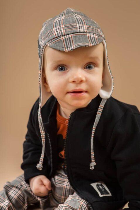 Junge trägt graue Schottenmuster karierte Baby Fliegermütze Hut Kappe mit Schirm Schildmütze - Schwarze Sweatjacke mit Bären Patch Reißverschluss - Braunen Wickelbody Bär von Pinokio - Babyphoto Kinderphoto