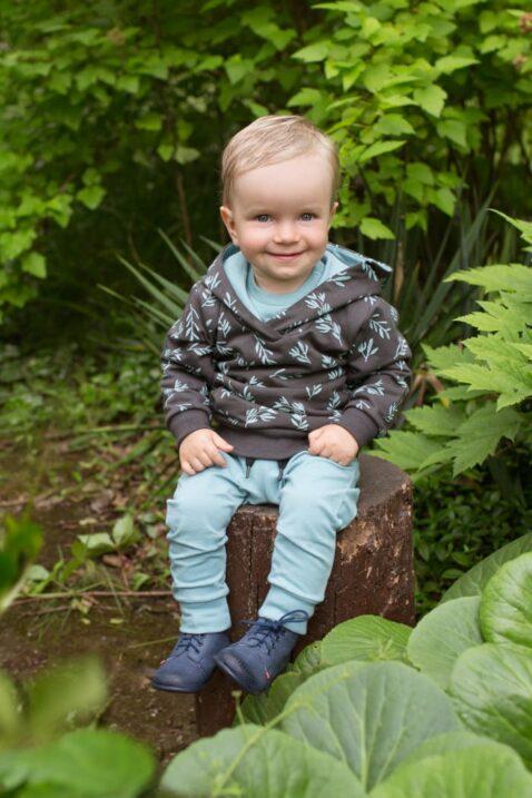 Lächelnder Junge trägt Baby Kinder Hoodie in Braun Graphit mit Zweige & Blätter, Patch STAY GREEN - Türkise Leggings Schlupfhose Komfortbund & Kordel von Pinokio - Babyphoto Kinderphoto