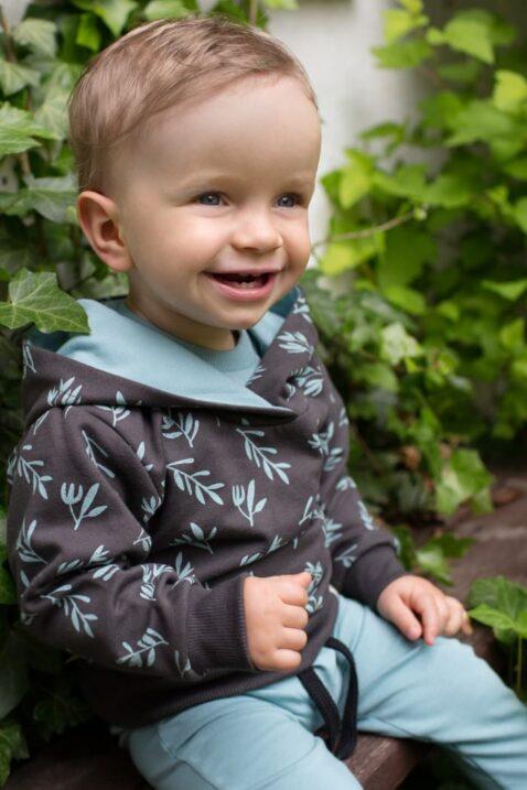Lachender sitzender Junge trägt Baby Kinder Kapuzenpullover in Braun mit Zweige Blätter All Over Muster - Lange Hose Leggings mit Patch STAY GREEN in Türkis Grün von Pinokio - Kinderphoto Babyphoto