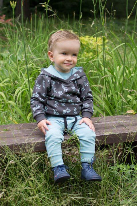 Sitzender Junge trägt Baby Kinder Leggings Sweathose mit Patch STAY GREEN Motto in Türkis - Kapuzenpullover Braun Graphit mit Zweige & Blätter von Pinokio - Babyphoto Kinderphoto