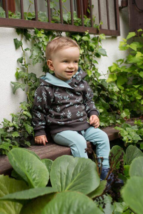 Lächelnder Junge trägt grüne türkise Baby Leggings Babyhose Sweathose mit Satement Patch Umwelt - Braunen Kinder-Hoodie mit Zweige & Blätter Muster von Pinokio - Kinderphoto Babyphoto