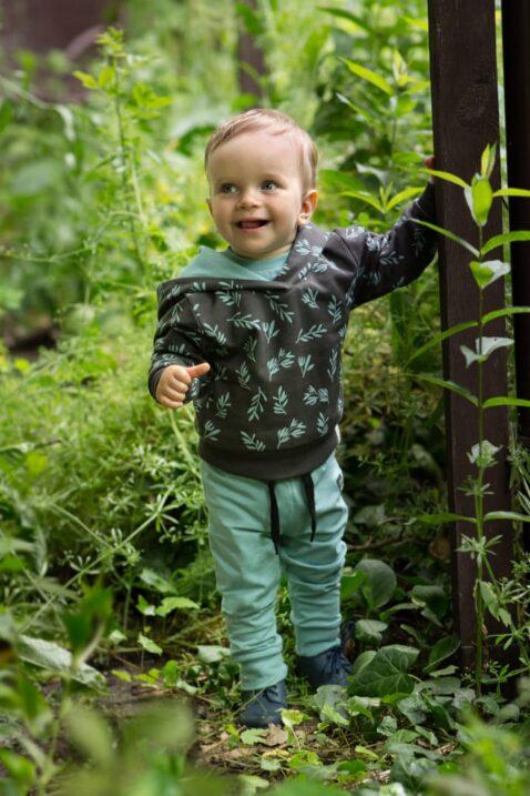 Stehender lächelnder Junge im Wald trägt Baby Kinder Kapuzenpullover in Braun Oker mit Zweige & Blätter - Leggings Babyhose in Türkis grün mit Patch STAY GREEN von Pinokio - Babyphoto Kinderphoto