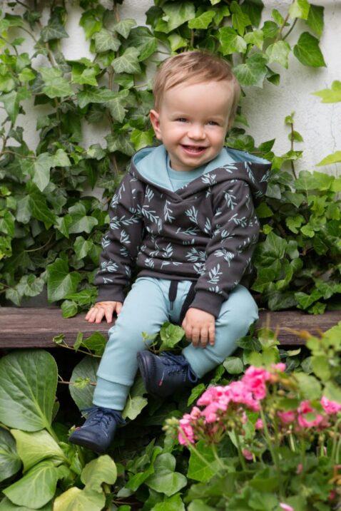 Sitzender lachender Junge trägt Kinder Baby Leggings Schlupfhose Türkis mit Patch Statement STAY GREEN - Hoodie in Braun mit Zweige & Blätter All Over Muster von Pinokio - Babyphoto Kinderphoto