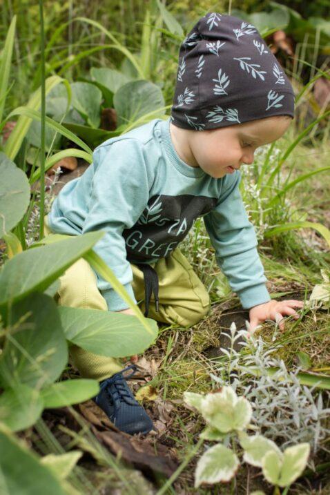 Spielender Junge trägt braune Mütze mit Blätter & Eule Patch - Grün Türkises Sweatshirt Langarmshirt langarm STAY GREEN Statement - Pumphose mit Tasche in Grün von Pinokio - Babyphoto Kinderphoto