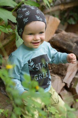 Lächelnder Junge trägt grüne Kinder Baby Pumphose mit Tasche - Braune Mütze mit Blätter & Patch Eule - Türkis grünes Oberteil Langarmshirt STAY GREEN von Pinokio - Babyphoto Kinderphoto