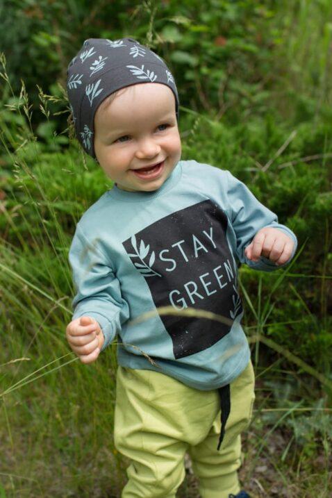 Lachender Junge trägt türkis gruenes Langarmshirt STAY GREEN Statement - Pumphose Haremshose mit Tasche & Kordel in Grün - Braune Mütze mit Patch Eule & Kauz von Pinokio - Babyphoto Kinderphoto