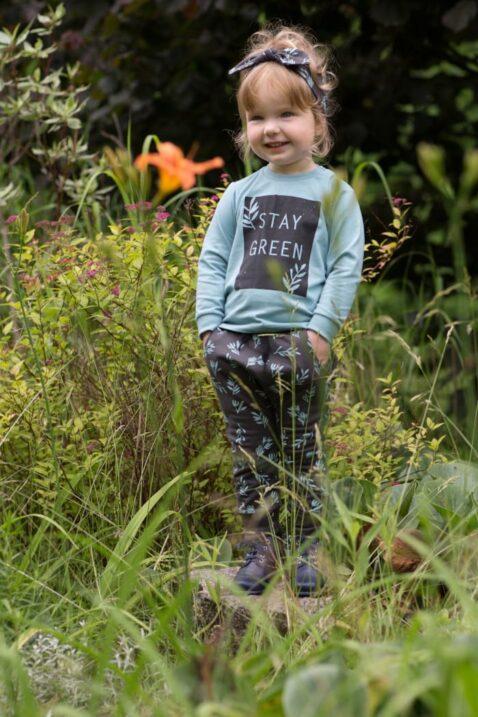 Lachendes Mädchen trägt Baby Kinder braune Pumphose mit Blätter & Komfortbund - Türkis grünes Oberteil Langarm STAY GREEN - Stirnband mit Schleife von Pinokio - Babyphoto Kinderphoto