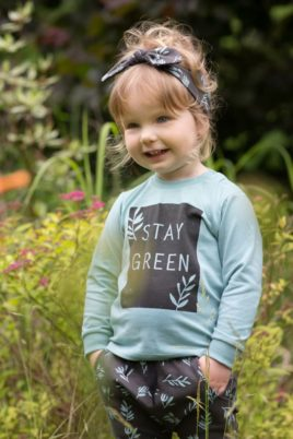 Stehendes Kinder Mädchen trägt Baby grünes Sweatshirt langarm STAY GREEN - Haremshose mit Blätter in Braun gemustert - Stirnband mit Schleife von Pinokio - Babyphoto Kinderphoto