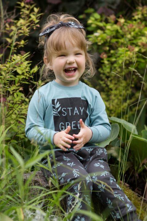Lachendes Mädchen trägt Baby Kinder türkis grünes Langarm Shirt STAY GREEN Statement - Braunes Stirnband & Pumphose mit Zweige & Blätter Muster mit Kordel von Pinokio - Babyphoto Kinderphoto