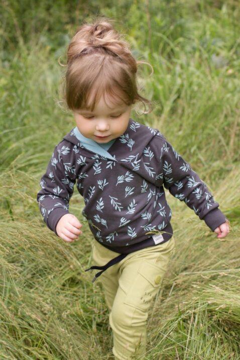 Laufendes Mädchen trägt grüne Baby Kinder Haremshose Schlupfhose mit Tasche & STAY GREEN Print - Kapuzenpullover mit türkisen Blättern gemustert Braun von Pinokio - Babyphoto Kinderphoto