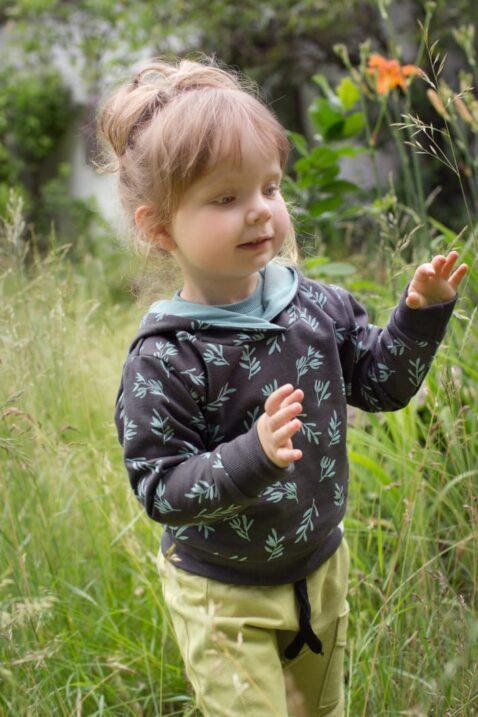 Stehendes Mädchen trägt braunen Kinder Baby Hoodie mit türkis grünen Blätter Muster - Grüne Pumphose Schlupfhose mit Tasche STAY GREEN Print von Pinokio - Babyphoto Kinderphoto